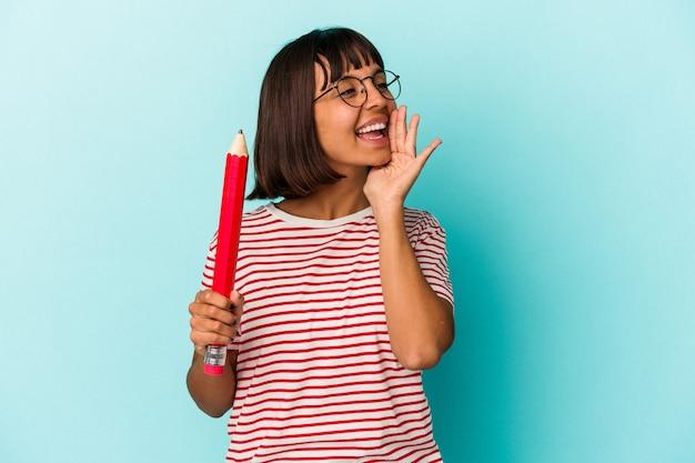 青い背景に分離された大きな鉛筆を持って叫び、開いた口の近くで手のひらを保持している若い混血の女性。