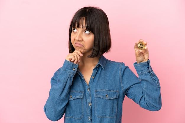 Молодая женщина смешанной расы держит биткойн изолированный фон и смотрит вверх