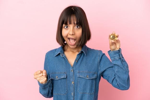 Молодая женщина смешанной расы, держащая биткойн изолированный фон, празднует победу в позиции победителя