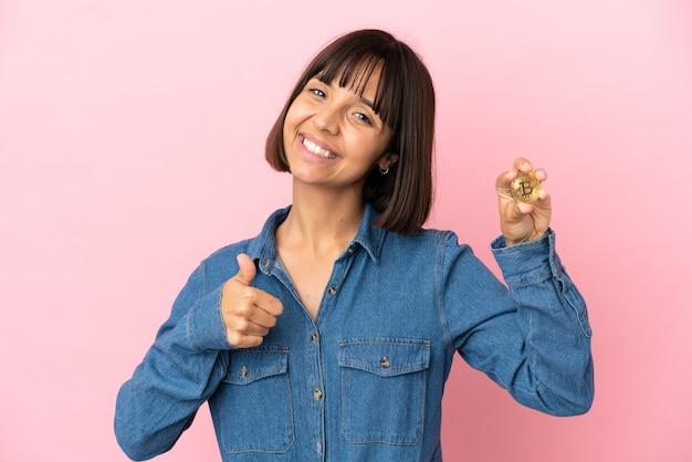 Молодая женщина смешанной расы, держащая биткойн изолированный фон, показывающая жест