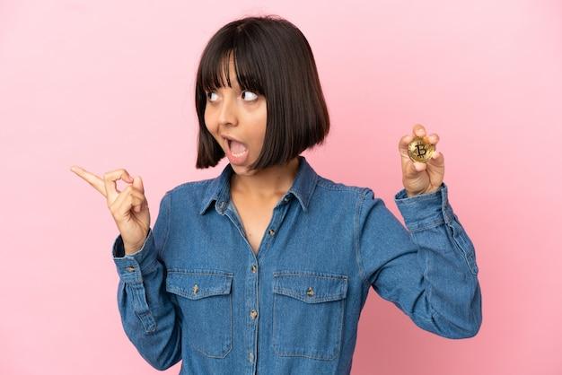 Молодая женщина смешанной расы держит биткойн изолированный фон, намереваясь реализовать решение, подняв палец вверх
