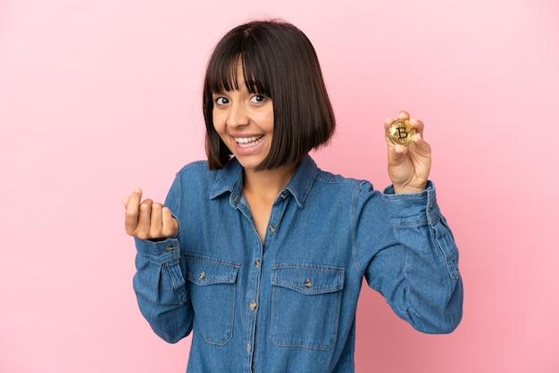 Молодая женщина смешанной расы, держащая биткойн изолированный фон, делая денежный жест