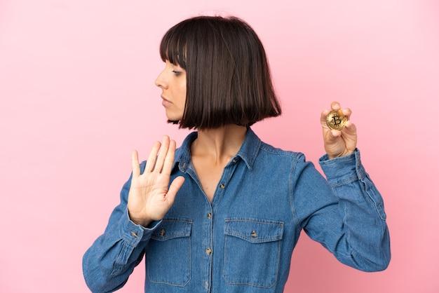 Молодая женщина смешанной расы держит биткойн изолированный фон, делая жест стоп и разочарованный