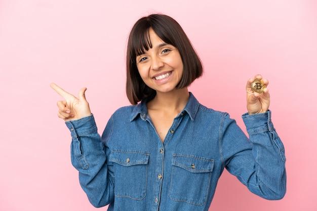 Молодая женщина смешанной расы, держащая биткойн изолированный фон, указывая пальцем в сторону