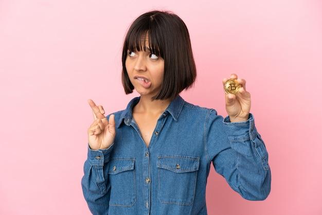 Молодая женщина смешанной расы держит биткойн изолированный фон со скрещенными пальцами и желает лучшего