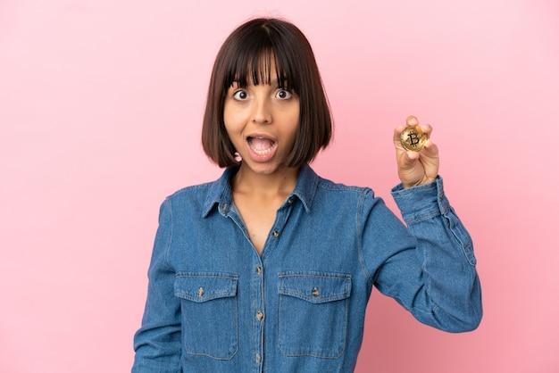 Молодая женщина смешанной расы, держащая биткойн изолированный фон с удивленным выражением лица