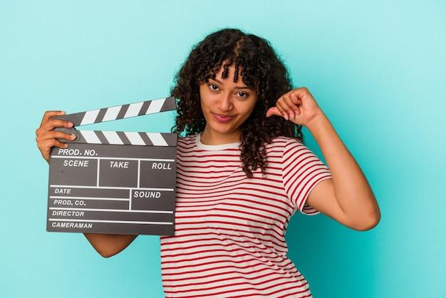 Молодая женщина смешанной расы, держащая с 'хлопушкой', изолированную на синем фоне, чувствует себя гордой и уверенной в себе, примером для подражания.