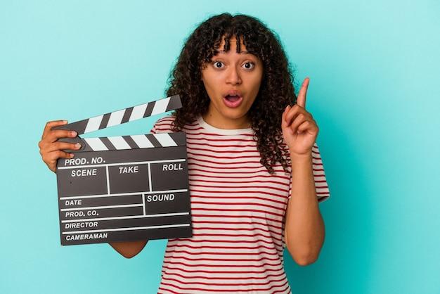 アイデア、インスピレーション コンセプトを持つ青の背景に分離されたカチンコを保持している若い混血女性。