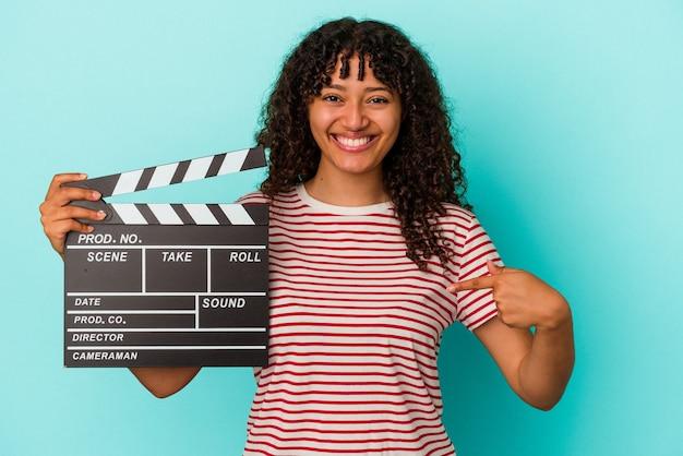 青の背景にカチンコを持つ若い混血の女性が、シャツのコピースペースを手で指し、誇りと自信を持って