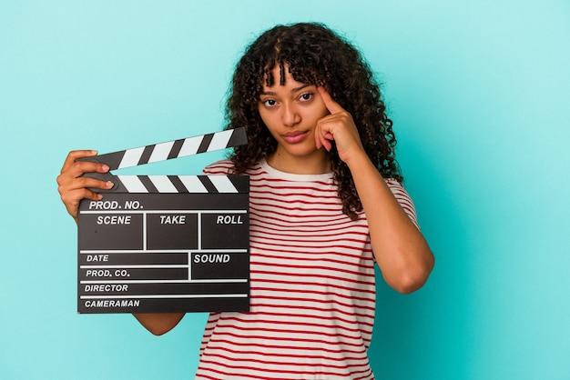 Молодая женщина смешанной расы, держащая с 'хлопушкой', изолированная на синем фоне, указывая висок пальцем, думая, сосредоточилась на задаче.