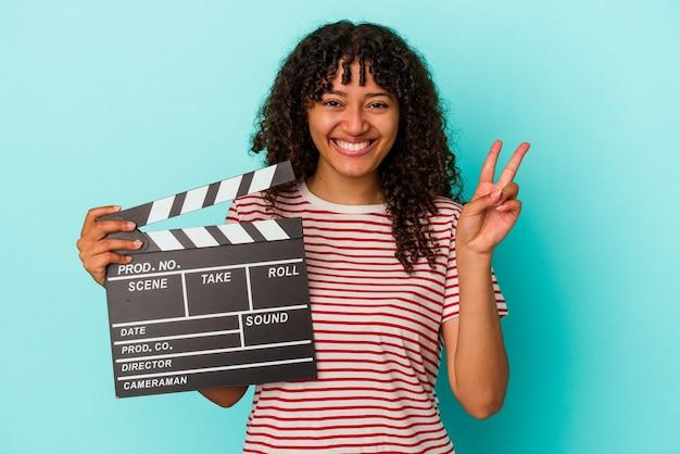 指で 2 番を示す青い背景に分離されたカチンコを保持している若い混血女性。