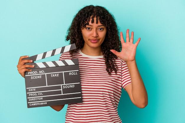 青い背景に分離されたカチンコを保持している若い混血の女性は、指で 5 番を示す陽気な笑顔を浮かべています。