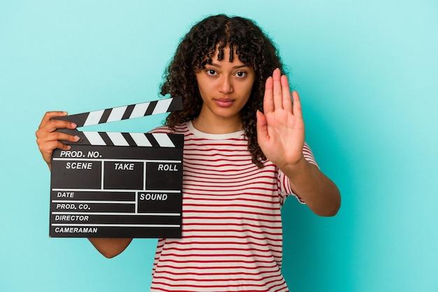 青の背景に分離されたカチンコを持った若い混血の女性が、一時停止の標識を示して手を差し伸べて立って、あなたを防ぎます。