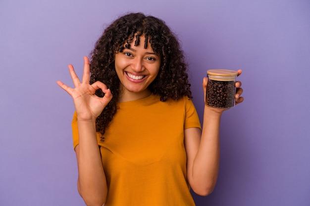 紫色の背景に分離されたコーヒー豆のボトルを保持している若い混血の女性は、陽気で自信を持って大丈夫なジェスチャーを示しています。