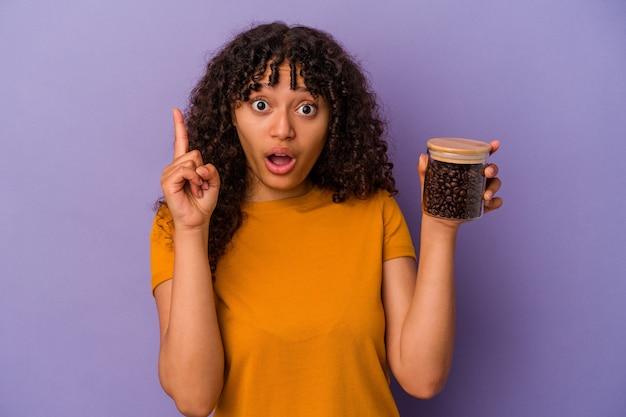 アイデア、インスピレーションの概念を持つ紫色の背景に分離されたコーヒー豆のボトルを保持している若い混血の女性。