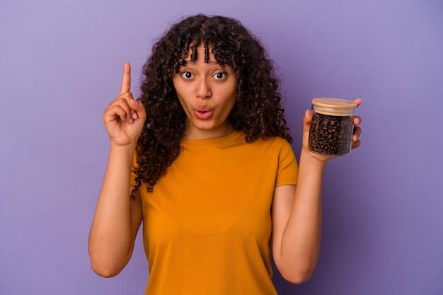 紫色の背景にコーヒー豆の瓶を持った若い混血女性が、素晴らしいアイデア、創造性のコンセプトを持っている。