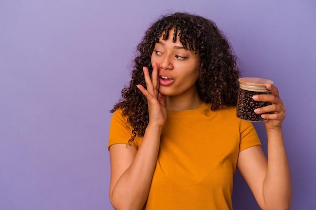 紫色の背景で隔離のコーヒー豆のボトルを保持している若い混血の女性は、秘密の熱いブレーキングニュースを言って脇を見ています