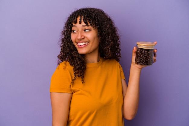 紫色の背景に分離されたコーヒー豆のボトルを保持している若い混血の女性は、笑顔、陽気で楽しい脇に見えます。