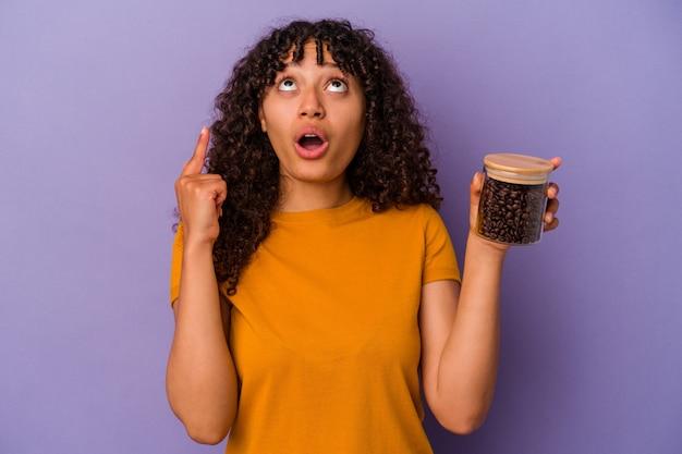 口を開けて逆さまを指している紫色の背景に分離されたコーヒー豆のボトルを保持している若い混血の女性。