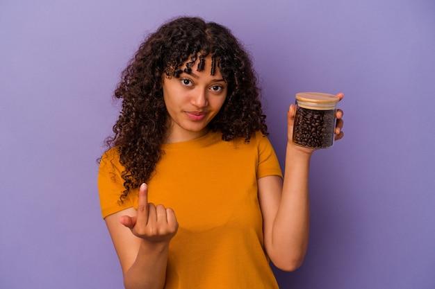 紫色の背景に隔離されたコーヒー豆のボトルを持っている若い混血の女性は、招待が近づくようにあなたに指を指しています。