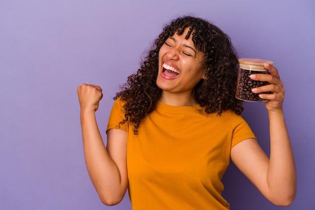 勝利、勝者の概念の後に拳を上げる紫色の背景に分離されたコーヒー豆のボトルを保持している若い混血の女性。