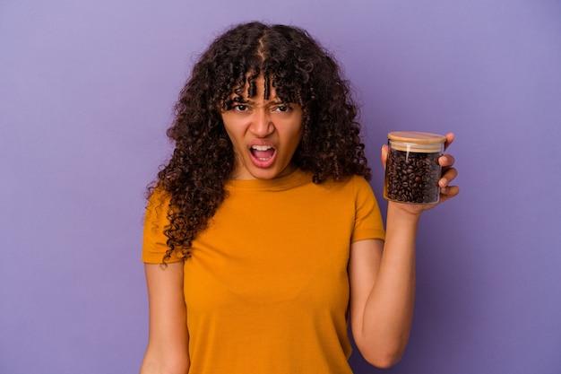 紫色の背景に分離されたコーヒー豆の瓶を持った若い混血の女性が、非常に怒って積極的に叫んでいます。
