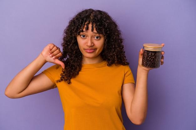 嫌いなジェスチャーを示す紫色の背景に分離されたコーヒー豆のボトルを保持している若い混血の女性、親指を下に。不一致の概念。