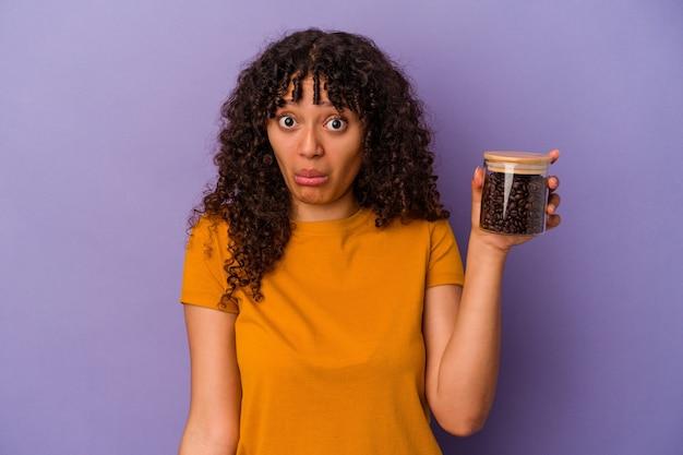 紫色の背景に分離されたコーヒー豆のボトルを保持している若い混血の女性は、肩をすくめ、目を開けて混乱します。