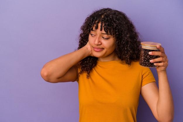頭の後ろに触れて、考えて選択を行う紫色の背景に分離されたコーヒー豆のボトルを保持している若い混血の女性。