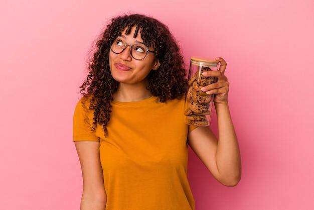 Молодая женщина смешанной расы держит банку с печеньем, изолированную на розовом фоне, мечтает о достижении целей и задач