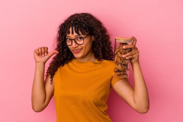 ピンクの背景に分離されたクッキーの瓶を保持している若い混血の女性は、誇りと自信を感じています。