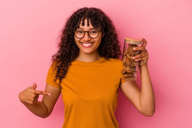 誇りと自信を持って、シャツのコピースペースを手で指しているピンクの背景の人に分離されたクッキーの瓶を保持している若い混血の女性
