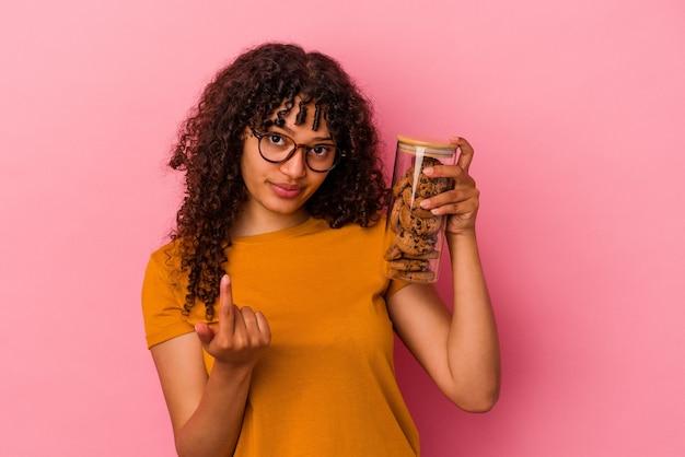 Молодая женщина смешанной расы держит банку печенья, изолированную на розовом фоне, указывая пальцем на вас, как будто приглашая подойти ближе.