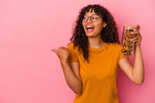 Молодая женщина смешанной расы, держащая банку печенья, изолированную на розовом фоне, указывает пальцем далеко, смеясь и беззаботно.