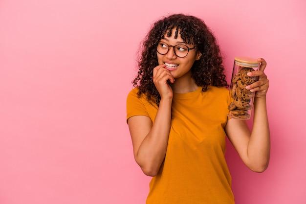 ピンクの背景に分離されたクッキーの瓶を保持している若い混血の女性は、コピースペースを見ている何かについて考えてリラックスしました。