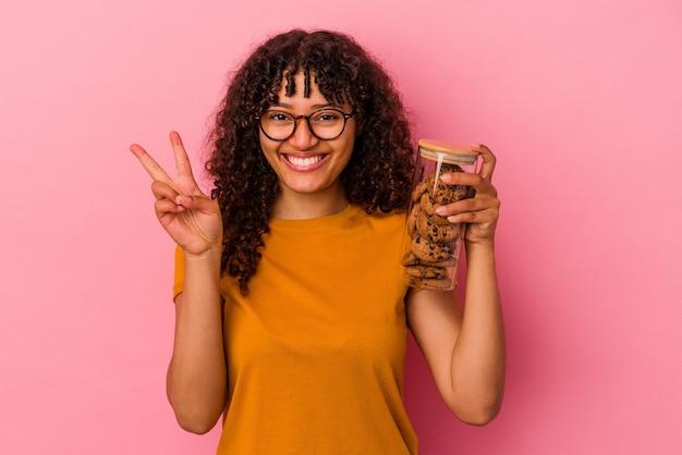 ピンクの背景に分離されたクッキーの瓶を持っている若い混血の女性は、指で2番目を示しています。