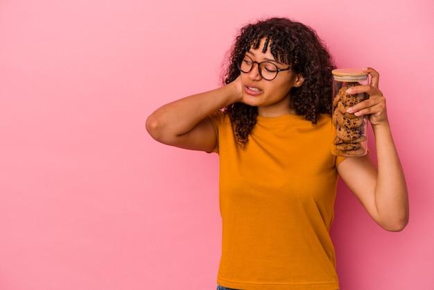 頭の後ろに触れて、考えて、選択をするピンクの背景に分離されたクッキーの瓶を保持している若い混血の女性。