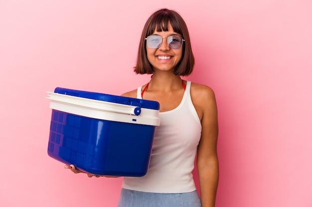 ピンクの背景に分離されたクーラーを保持している若い混血の女性は幸せ、笑顔、陽気な。