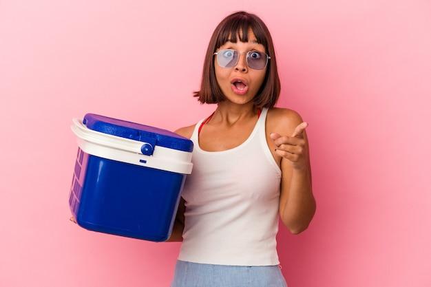 アイデア、インスピレーションのコンセプトを持つピンクの背景に分離されたクーラーを保持している若い混血の女性。