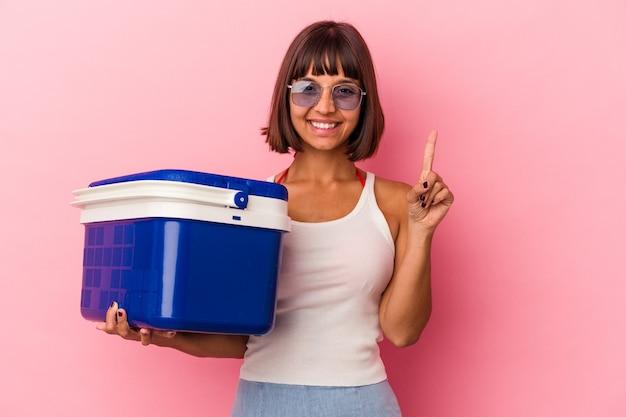 ピンクの背景に分離されたクーラーを保持している若い混血の女性は、指でナンバーワンを示しています。
