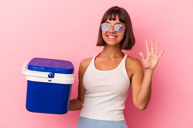 ピンクの背景に分離されたクーラーを保持している若い混血の女性は、指で5番を示して陽気に笑っています。