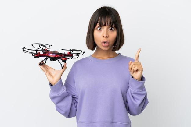 Молодая женщина смешанной расы, держащая дрон, изолированная на белом фоне, намеревается реализовать решение, поднимая палец вверх
