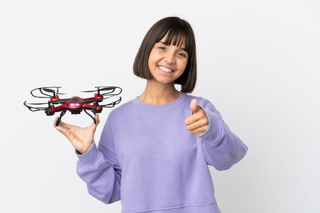 Молодая женщина смешанной расы держит дрон на белом фоне с большими пальцами руки вверх, потому что произошло что-то хорошее