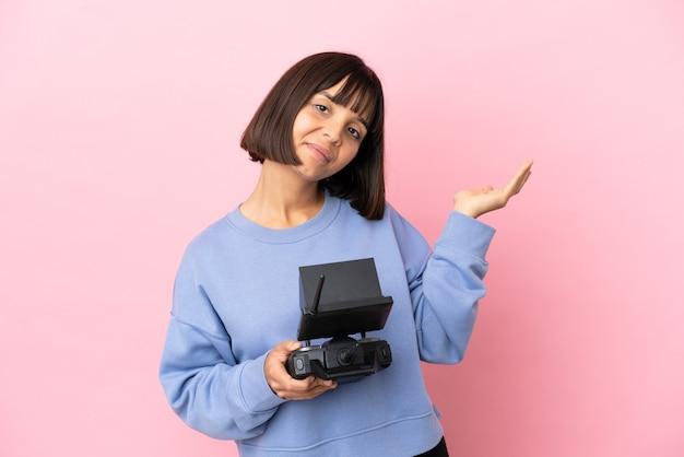 Молодая женщина смешанной расы, держащая пульт дистанционного управления дроном, изолированная на розовом фоне, протягивает руки в сторону для приглашения приехать