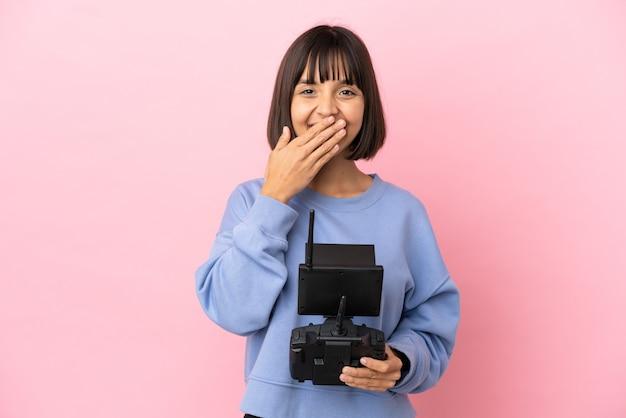 ピンクの背景に分離されたドローンのリモコンを保持している若い混血の女性幸せと笑顔の手で口を覆う