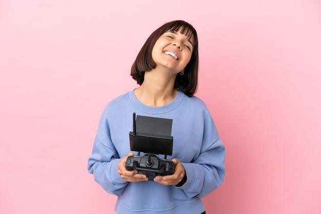 Молодая женщина смешанной расы, держащая пульт дистанционного управления дроном, изолированная на розовом фоне смеясь Premium Фотографии