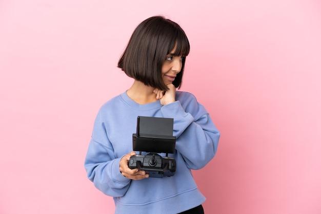 Молодая женщина смешанной расы, держащая пульт дистанционного управления дроном, изолированная на розовом фоне, глядя вверх, улыбаясь Premium Фотографии
