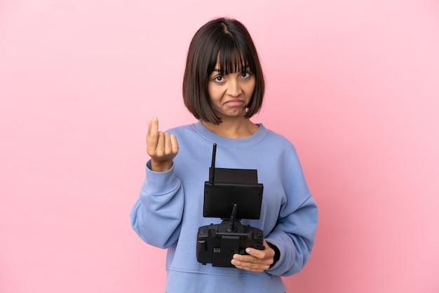Молодая женщина смешанной расы, держащая пульт дистанционного управления дроном, изолированная на розовом фоне, делая денежный жест