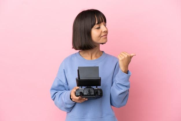 製品を提示する側を指しているピンクの背景に分離されたドローンのリモコンを保持している若い混血の女性