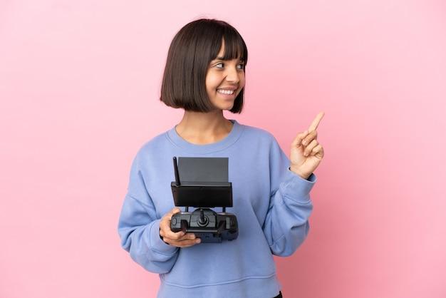 素晴らしいアイデアを指しているピンクの背景に分離されたドローンのリモコンを保持している若い混血の女性